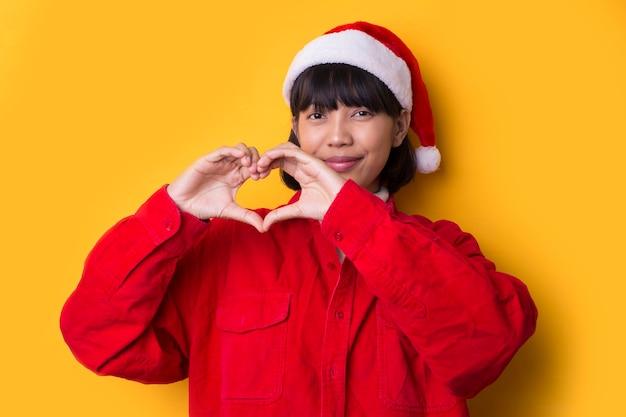 Aziatisch meisje gekleed in santahoed met een gebaar van de kerstmisliefde