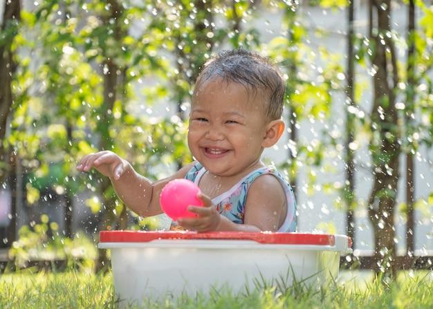 Aziatisch meisje gelukkig en glimlach in mand op gras, aziatische kinderen gelukkig en bal spelen bij de hand in haar huis tijdens coronavirus of covid-19 pandemie