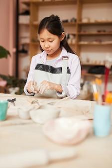 Aziatisch meisje genieten van aardewerk klasse