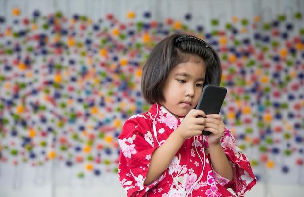 Aziatisch meisje glimlach met oortelefoon en mobiele telefoon