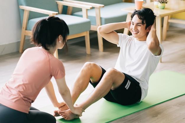 Aziatisch meisje houdt de voeten van haar vriend vast om crunches te doen