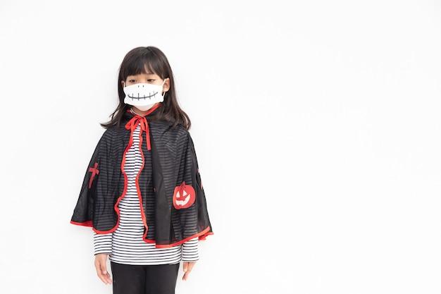 Aziatisch meisje in een halloween-kostuum met een medisch masker halloween met veiligheid van covid19