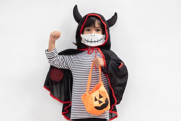 Aziatisch meisje in een halloween-kostuum met een medisch masker. halloween met veiligheidsmaatregelen van covid-19