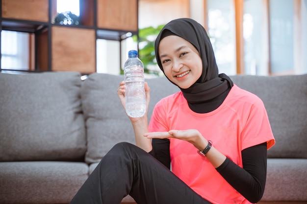 Aziatisch meisje in een sluier sportkleding glimlacht terwijl ze een drinkfles vasthoudt met handgebaren biedt iets zittend op de vloer tijdens het sporten binnenshuis thuis