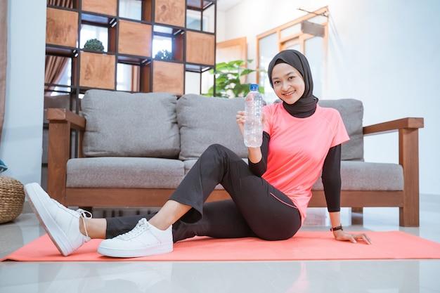 Aziatisch meisje in een sluier sportkleding glimlacht terwijl ze een drinkfles vasthoudt terwijl ze op de grond zit met een mat terwijl ze binnenshuis traint