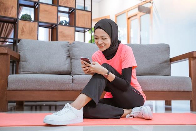 Aziatisch meisje in hijab sportkleding glimlacht kijken naar een mobiele telefoon zittend op de vloer met een bankmuur thuis