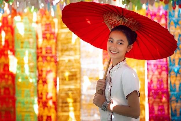 Aziatisch meisje in noordelijk traditioneel kostuum en rode paraplu