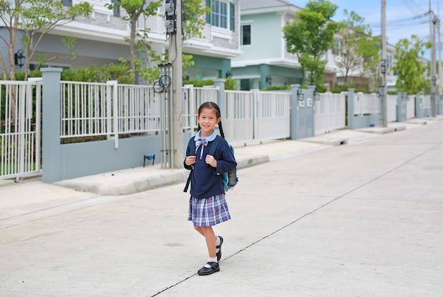 Aziatisch meisje in schooluniform die een medisch masker dragen dat op straat loopt