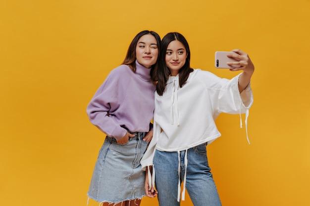 Aziatisch meisje in spijkerrok en paarse trui knipoogt. aantrekkelijke brunette vrouw in jeans en witte hoodie houdt telefoon vast