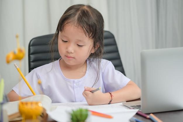 Aziatisch meisje in voorschools eenvormig doend schoolhuiswerk die en thuis trekken trekken