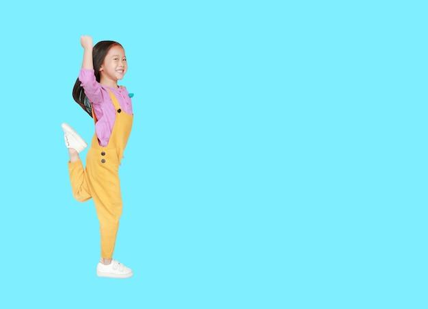 Aziatisch meisje in werkbroeken die of over cyaan met exemplaarruimte springen lopen.