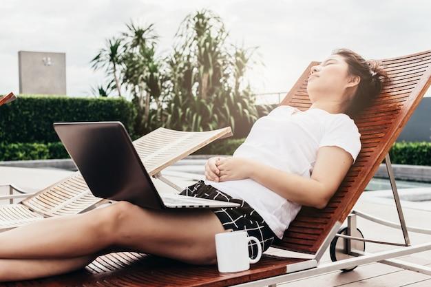 Aziatisch meisje in witte t-shirt werken met laptop en een koffiekopje in lui en ontspannen poseren