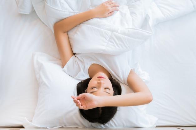 Aziatisch meisje is hoofdpijn in bed. top uitzicht
