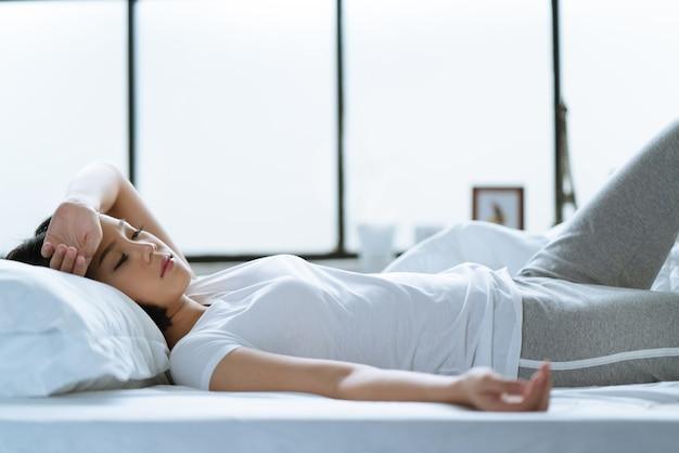 Aziatisch meisje is hoofdpijn in bed.