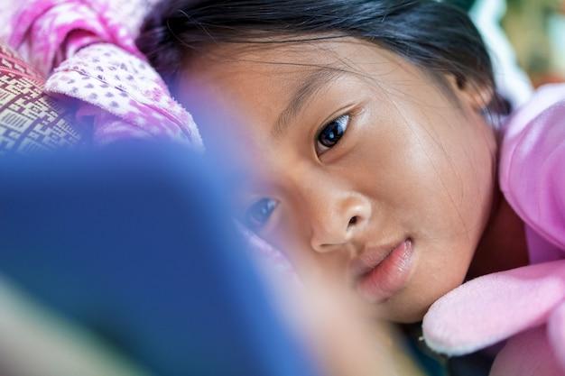 Aziatisch meisje kijkt 's nachts vrolijk naar tekenfilms op haar smartphone in haar bed.