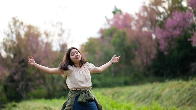 Aziatisch meisje lacht ondeugend en draait zich naar de camera tijdens een natuurreis, ze spreidde beide armen.