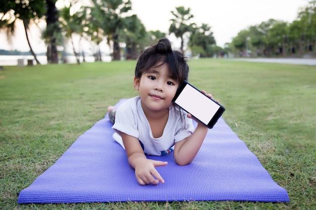 Aziatisch meisje liggen op de buik met mobiel