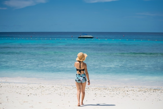 Aziatisch meisje met bikini en hoed op wit zandstrand van similan-eiland