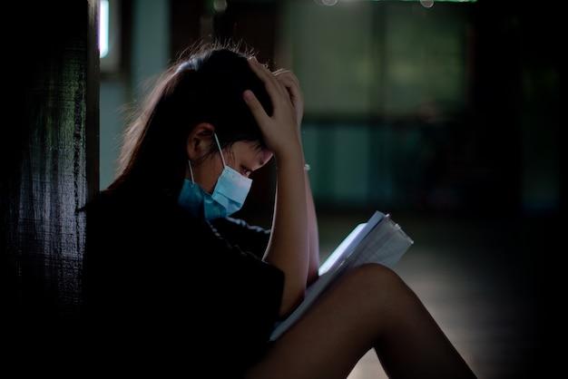Aziatisch meisje met een masker zit en leest een boek met stress en begrijpt het niet. concept van leerproblemen tijdens staatsquarantaine