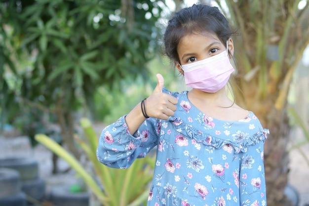 Aziatisch meisje met gezichtsmasker voor bescherming covid19 coronavirus en duimen omhoog