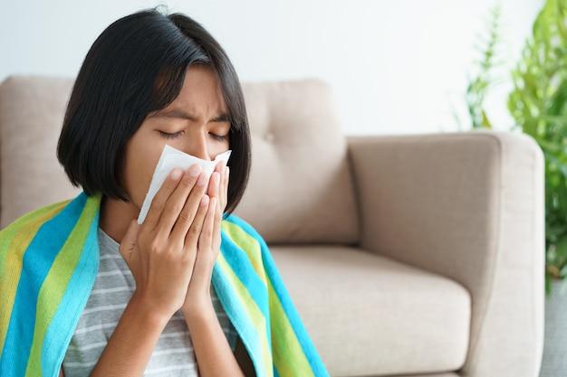 Aziatisch meisje met griepseizoen en niezen met behulp van papieren zakdoekjes zittend in de woonkamer thuis.