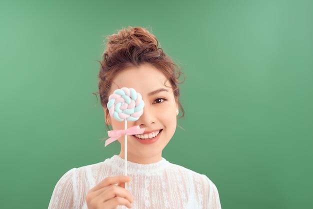 Aziatisch meisje met grote snoep op een stokje, met een lolly in de hand