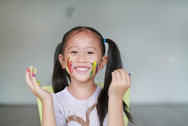 Aziatisch meisje met haar kleurrijke handen en wang geschilderd in de kinderkamer.