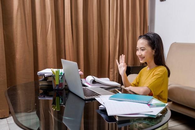 Aziatisch meisje met laptop die thuis online schoolklas bijwoont. online onderwijs tijdens quarantaine