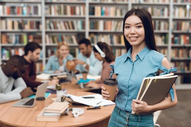 Aziatisch meisje met nota's en koffie in bibliotheek.