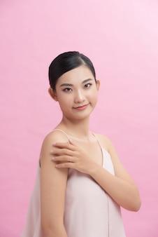 Aziatisch meisje met perfecte gloeiende huid en naakt natuurlijke make-up poseren tegen roze achtergrond.
