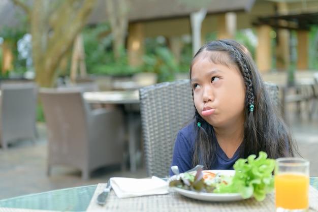 Aziatisch meisje met uitdrukking van afschuw tegen groenten