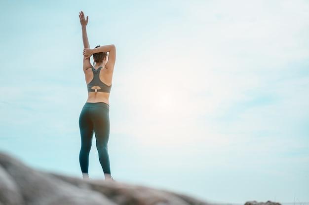 Aziatisch meisje oefent in het weekend oefeningen en strekt haar lichaam uit op het strand healthy