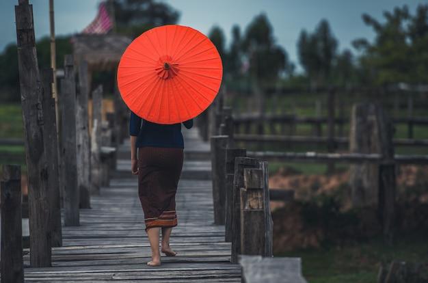 Aziatisch meisje op traditionele kleding met een rode paraplu die houten brug kruisen