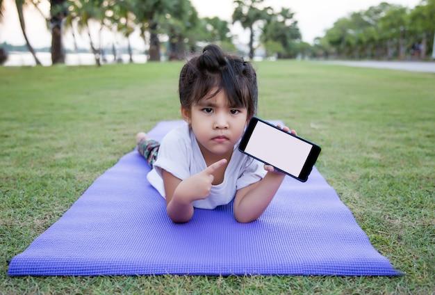 Aziatisch meisje op yogamat en mobiel