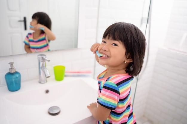 Aziatisch meisje poetst haar tanden en toont haar tanden bij het poetsen van haar tanden