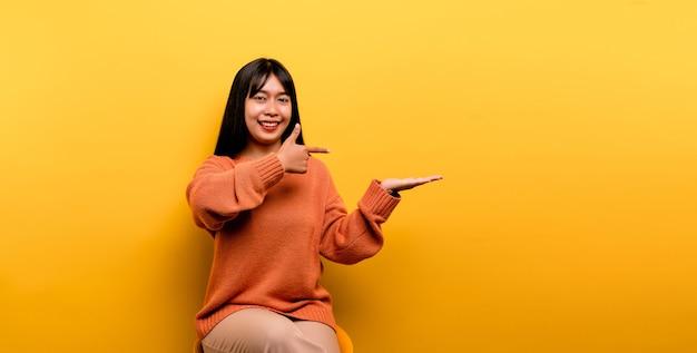 Aziatisch meisje pretty draagt een oranje casual kleding. gele achtergrond vier de overwinning met een gelukkige glimlach en de uitdrukking van de winnaar met een opgeheven hand. blije uitdrukking