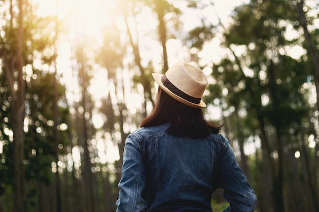 Aziatisch meisje reizen in het bos op vakantie, kijken naar het prachtige bos.