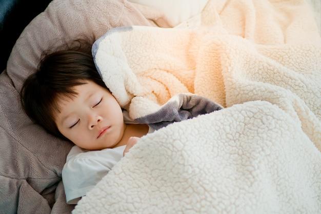 Aziatisch meisje slapen op bed, kind ziek, kind slapen