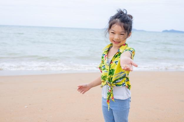 Aziatisch meisje speelt in het zand op het strand