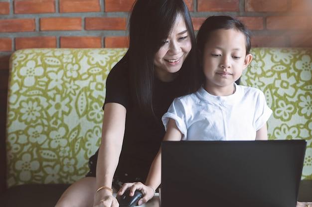 Aziatisch meisje spelen op laptop met haar moeder thuis.