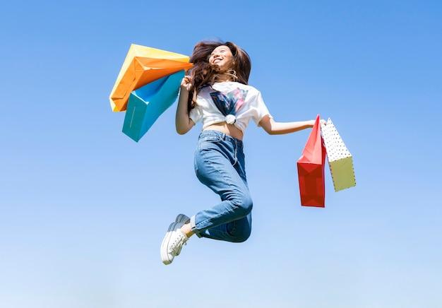 Aziatisch meisje springen met boodschappentassen
