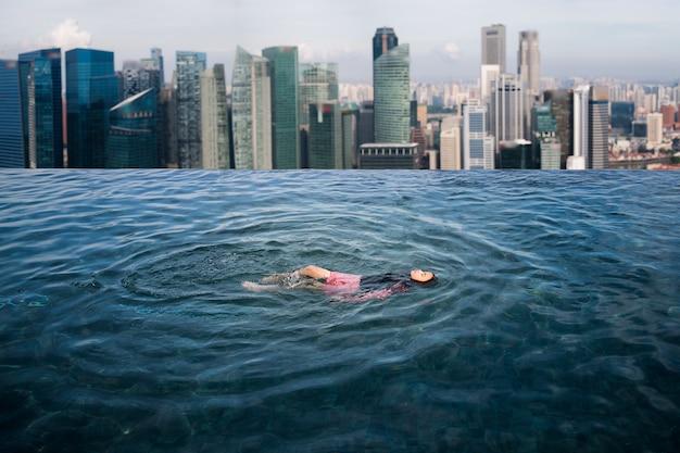 Aziatisch meisje swimmimg in het zwembad op het dak in het hotel