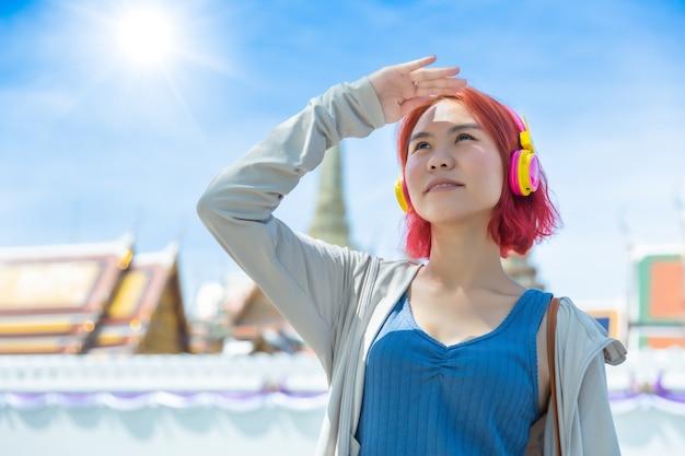 Aziatisch meisje tiener rood haar gekleurde staande buiten tegen hoge uv-zonlicht op zomerseizoen zonnige dag hemel thaise tempel.