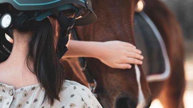 Aziatisch meisje van het schooljonge geitje met paard, het berijden of het beoefenen van paardrijden bij paardenboerderij.