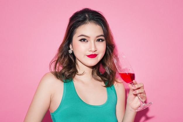 Aziatisch meisje vieren met professionele make-up en stijlvol kapsel met een glas champagne.