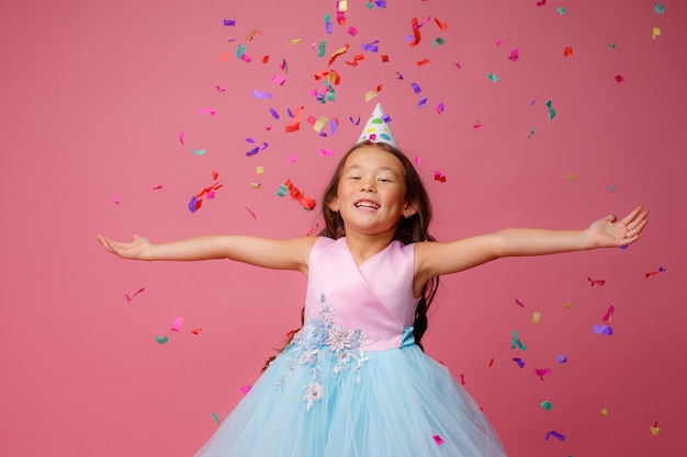 Aziatisch meisje viert verjaardag klappen vangt confetti op roze