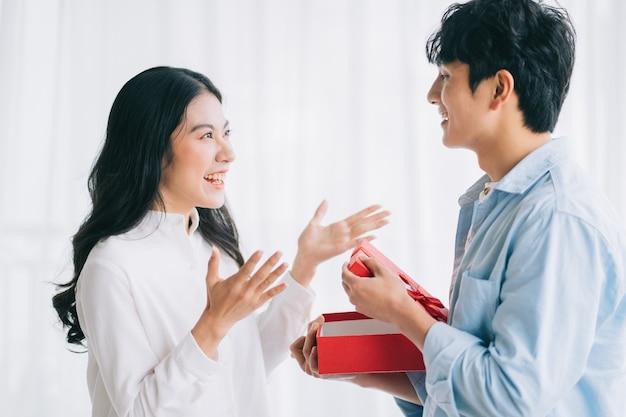 Aziatisch meisje voelt zich blij en verrast om op valentijnsdag geschenken te ontvangen van haar vriend