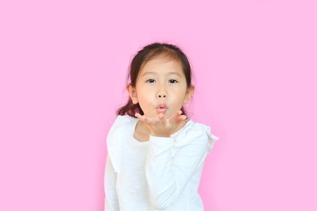 Aziatisch meisje waait kus met hand op lucht die mooi op roze is