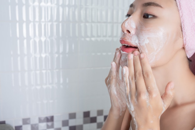 Aziatisch meisje wast gezicht.