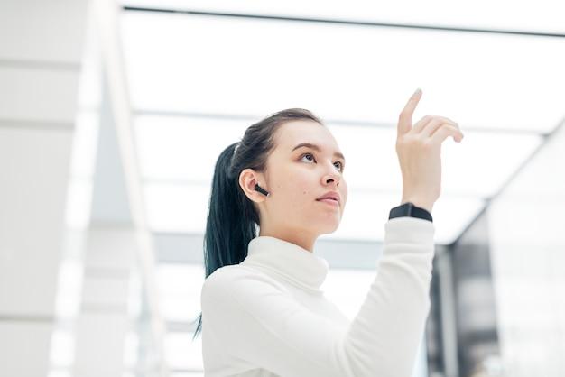 Aziatisch meisje wat betreft futuristische technologie op het virtuele scherm